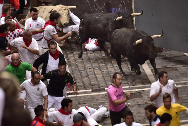 <p>Revellers run in front of Jandilla's fighting bulls during the running of the bulls at the San Fermin Festival, in Pamplona, northern Spain, July 11, 2017. Revellers from around the world flock to Pamplona every year to take part in the eight days of the running of the bulls. (AP Photo/Alvaro Barrientos) </p>