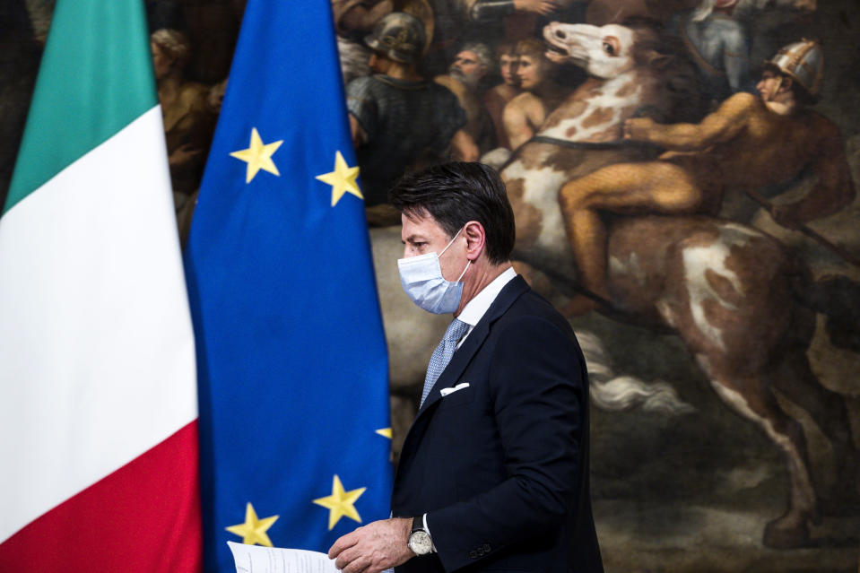 """Italian Premier Giuseppe Conte leaves after announcing new restrictions to curb the spread of coronavirus, in Rome, Wednesday, Nov. 4, 2020. Four regions in Italy are being put under severe lockdown, forbidding people to leave their homes except for essential reasons such as food shopping and work in a bid to slow surging COVID-19 infections and prevent hospitals from being overwhelmed. Premier Giuseppe Conte on Wednesday night announced what he described as """"very stringent"""" restrictions on the so-called """"red zone"""" regions of high risk: Lombardy, Piedmont, Valle d'Aosta in the north and Calabria, the region forming the """"toe"""" in the south of the Italian peninsula. (Angelo Carconi/Pool Photo via AP)"""