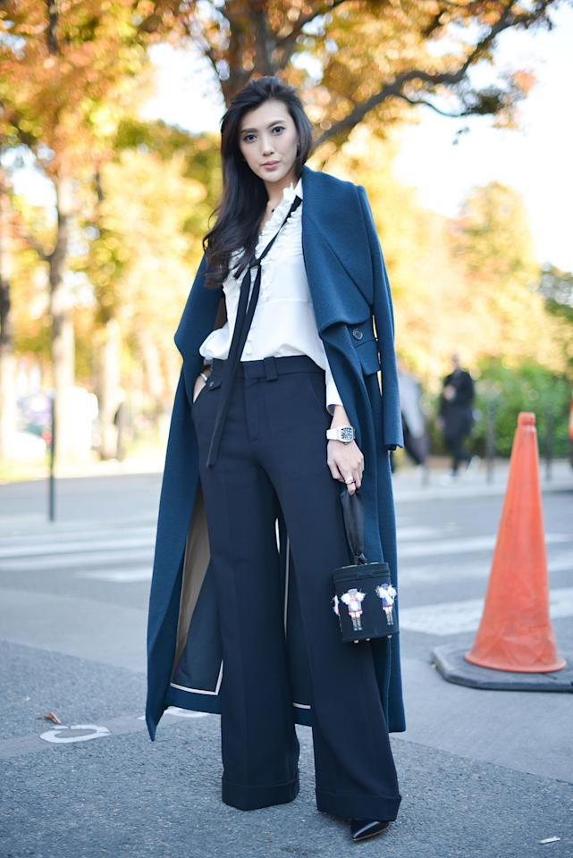 <p>Sophisticated mama! This Paris Fashion Week goer made her flare slacks and white top all the more stylish by draping a wool coat over her shoulders. (Getty Images)</p>