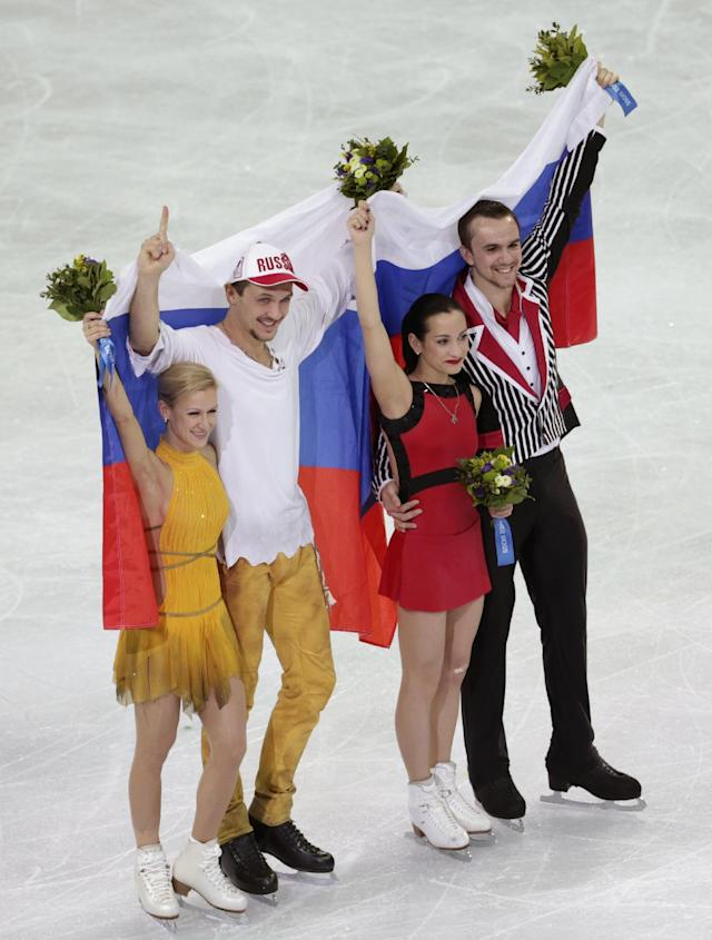 Tatiana Volosozhar and Maxim Trankov of Russia, left, and Ksenia Stolbova and Fedor Klimov of Russia celebrate after they placed first and second following the flower ceremony for the pairs free skate figure skating competition at the Iceberg Skating Palace during the 2014 Winter Olympics, Wednesday, Feb. 12, 2014, in Sochi, Russia. (AP Photo/Bernat Armangue)