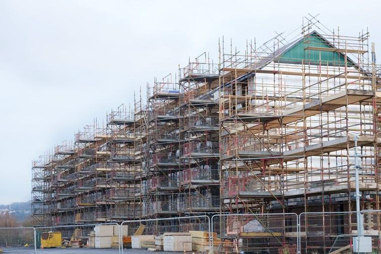 Large-scale construction project shroud in scaffolding against a pale sky