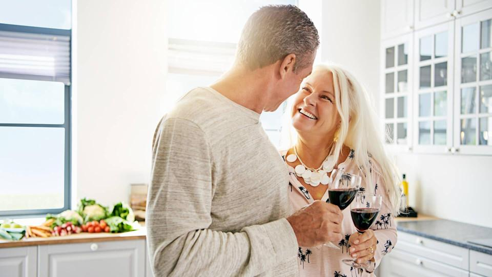 senior couple drinking wine in the kitchen together