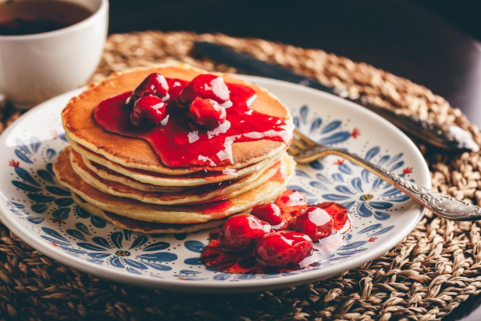 Stack of pancakes with dogberry jam on white plate with ornate