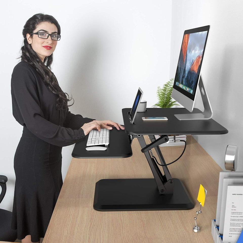 """<h3><strong>Standing Desk Under $125</strong></h3><br><br>This adjustable standing desk converter can transform any desk into an ergonomic work station. Offering a keyboard, mouse deck, and cup holder, this desk helps to reduce neck and back fatigue while working.<br><br><strong><a href=""""https://www.amazon.com/SLYPNOS-Height-Adjustable-Standing-Converter/dp/B078WN3RLQ/ref=sr_1_fkmrnull_3?crid=29O1GOR0SLFJM&keywords=slypnos+height+adjustable+standing+desk&qid=1556220087&s=gateway&sprefix=slypno%2Caps%2C125&sr=8-3-fkmrnull"""" rel=""""nofollow noopener"""" target=""""_blank"""" data-ylk=""""slk:What people are saying"""" class=""""link rapid-noclick-resp"""">What people are saying</a></strong>: """"This standing desk is a must have! I was really surprised at how well built this desk was. The desk is big enough to fit two large monitors and the keyboard tray is so wide so allows for the keyboard and mouse. The best part is nothing moves on the desk when [lowering] the unit and even when lifting the unit.""""<br><br><strong>SLYPNOS</strong> SLYPNOS Height Adjustable Standing Desk Riser, $, available at <a href=""""https://www.amazon.com/SLYPNOS-Height-Adjustable-Standing-Converter/dp/B078WN3RLQ/ref=sr_1_11?keywords=standing+desk&qid=1556219589&refinements=p_72%3A2661619011&rnid=2661617011&s=gateway&sr=8-11"""" rel=""""nofollow noopener"""" target=""""_blank"""" data-ylk=""""slk:Amazon"""" class=""""link rapid-noclick-resp"""">Amazon</a>"""