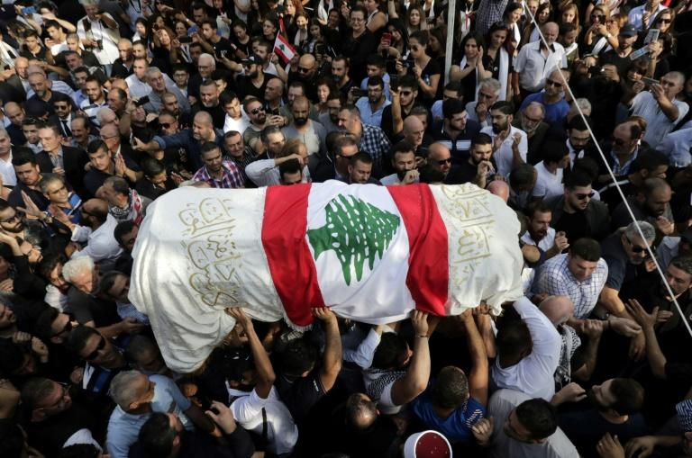 The coffin of slain Lebanese protester Alaa Abou Fakhr, draped in a national flag, is carried by mourners through the streets of his hometown of Chouaifet, southeast of Beirut, during his funeral procession on November 14, 2019 (AFP Photo/ANWAR AMRO)