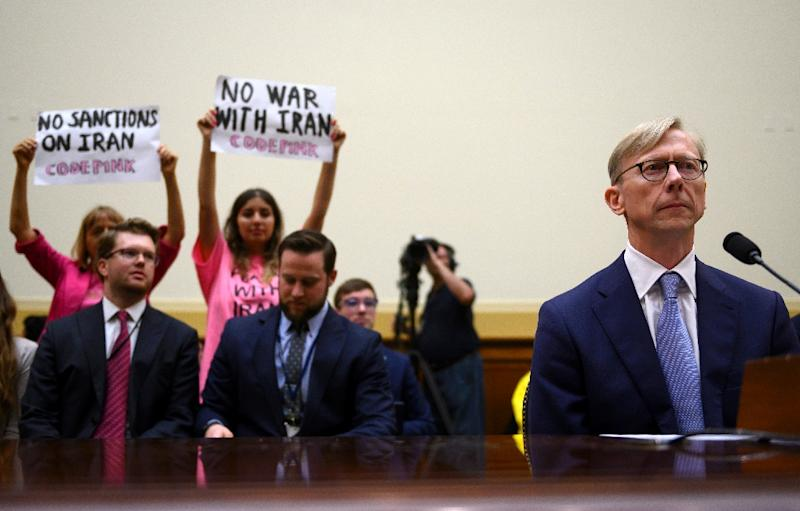 Protesters from pacifist group Code Pink hold up banners as Brian Hook, the US representative on Iran, testifies before a House Foreign Affairs subcommittee (AFP Photo/ANDREW CABALLERO-REYNOLDS)
