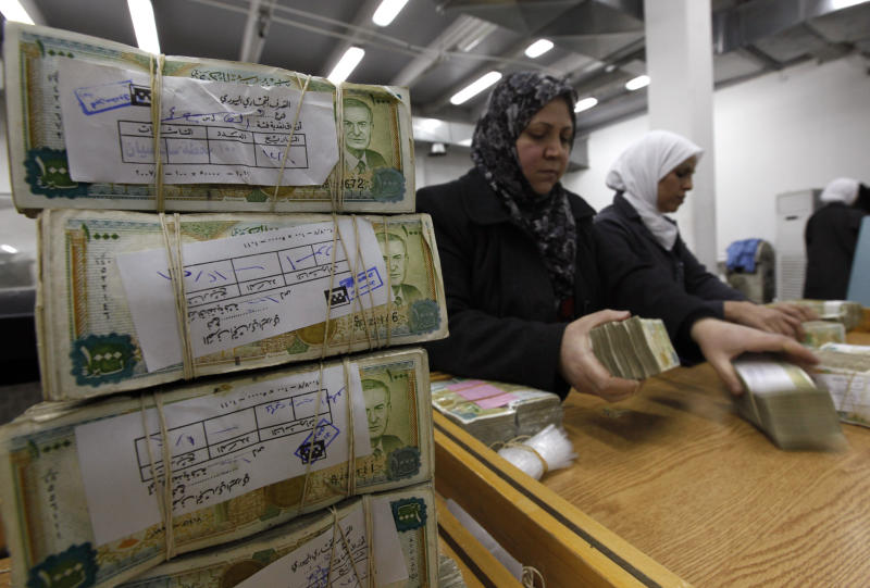 FILE - In this January 13, 2010 file photo, Syrian employees stack packets of Syrian currency in the Central Syrian Bank in, Damascus, Syria. With Syria's currency hitting record lows, a nationwide symbolic campaign has been launched by merchants, barbers, supermarkets and even gyms to support the Syrian pound. (AP Photo/Hussein Malla, File)