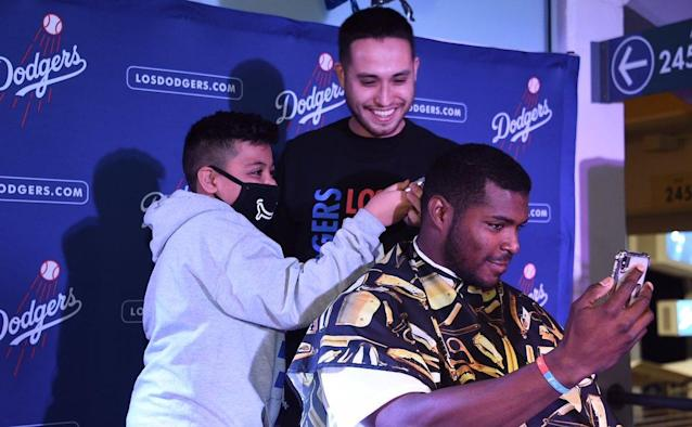 "<a class=""link rapid-noclick-resp"" href=""/mlb/players/9341/"" data-ylk=""slk:Yasiel Puig"">Yasiel Puig</a> gets a haircut from a kid battling cancer during Puig's Pizza and Shave Party. (Twitter/@Dodgers)"