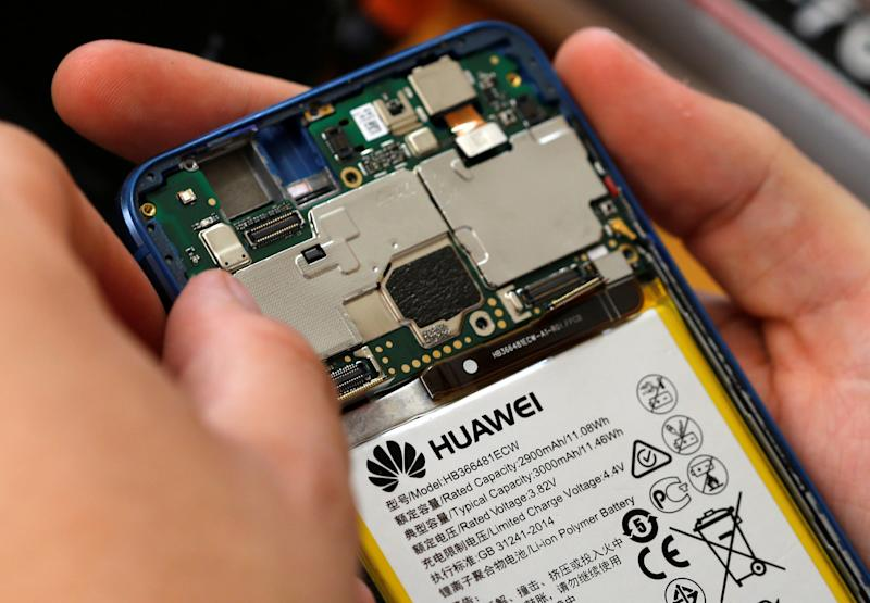 A worker refurbishes a Huawei cell phone at a workshop of the Oxflo company, specialised in refurbishment of broken European smartphones which will be resold and provided with a warranty as part of an eco-responsible approach, in Lusignac, France, June 20, 2019. REUTERS/ Regis Duvignau