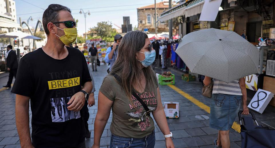 People wearing medical masks walk about at a market in the centre of Jerusalem on August 5, 2021. -