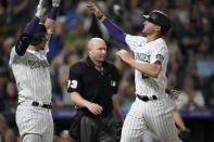 Colorado Rockies' Dom Nunez, left, congratulates Ryan McMahon, who scored on a double by Brendan Rodgers against the Milwaukee Brewers during the seventh inning of a baseball game Friday, June 18, 2021, in Denver. (AP Photo/David Zalubowski)