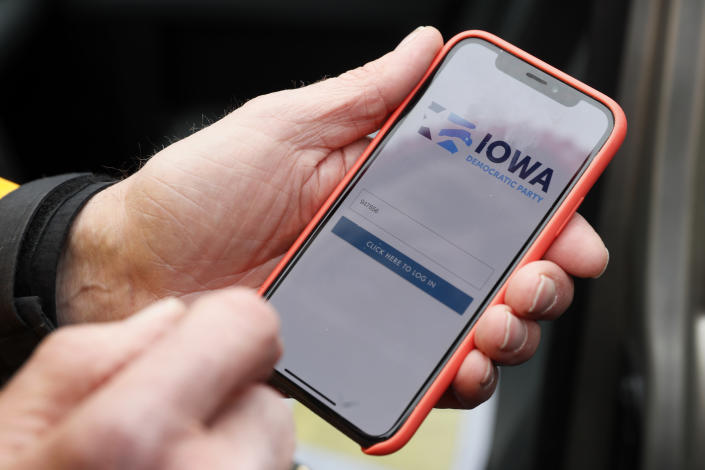 A precinct captain from Des Moines, Iowa, holds his iPhone that shows the Iowa Democratic Party's caucus reporting app in Nov. 2019. (Charlie Neibergall/AP)