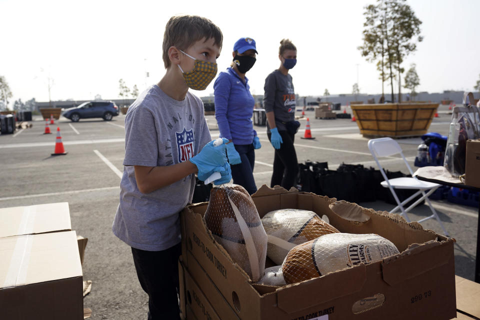Owen Demoff, 11, volunteers at a food distribution center set up at SoFi Stadium ahead of Thanksgiving and amid the COVID-19 pandemic, Monday, Nov. 23, 2020, in Inglewood, Calif. (AP Photo/Marcio Jose Sanchez)