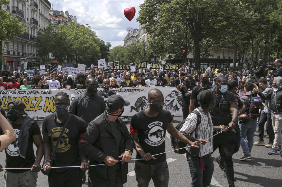 """People march during a protest in Paris, Saturday, June 20, 2020. Multiple protests are taking place in France on Saturday against police brutality and racial injustice, amid weeks of global anger unleashed by George Floyd's death in the US. Banner reads """"Let us breathe"""". (AP Photo/Rafael Yaghobzadeh)"""