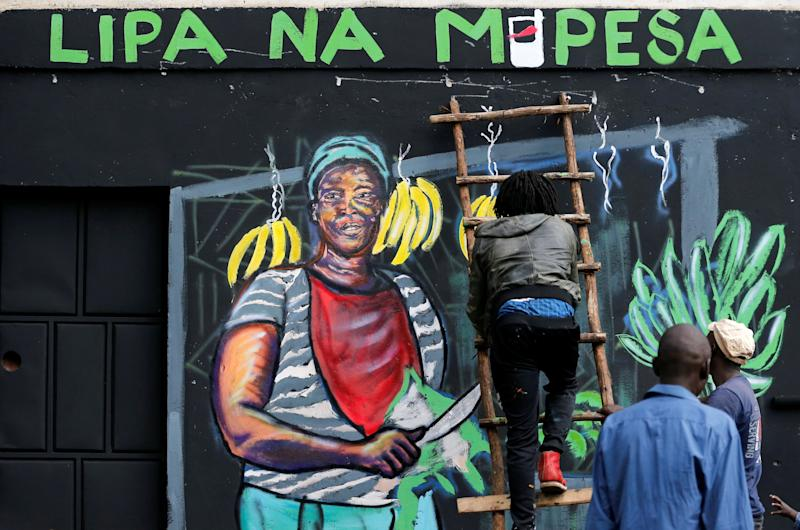 An artist works on a mural advocating for retail M-Pesa mobile phone cashless payments as a measure against the spread of the coronavirus disease. The mural depicts a female vendor selling bananas and green plantains.