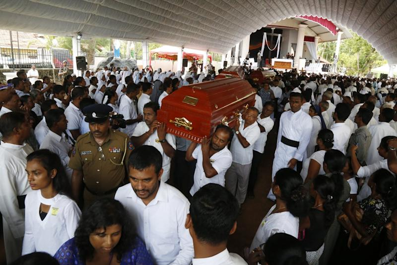 Coffins are carried to the graves during the mass funeral of the victims as Sri Lanka holds a day of mourning. (EPA)