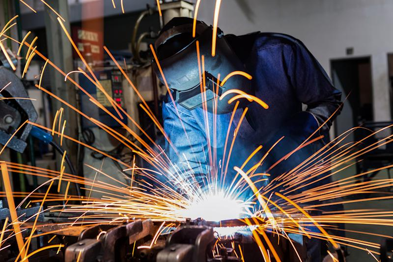 A man operating welding equipment, with sparks flying everywhere..