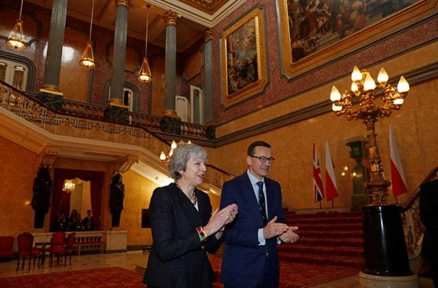 Theresa May and Mateusz Morawiecki applaud after hearing a choir sing during the consultations at Lancaster House