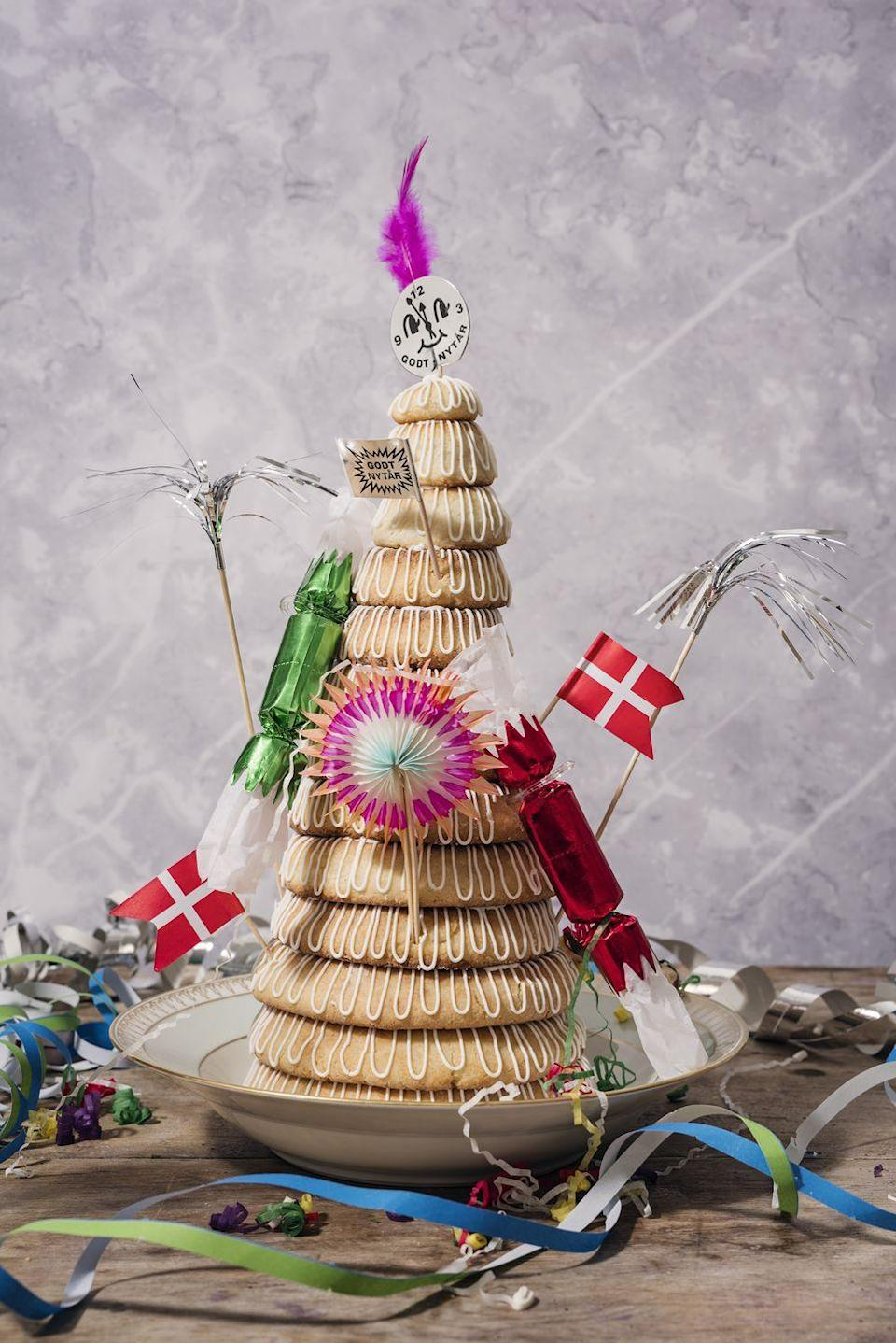 "<p>According to CNN, Kransekage is <a href=""https://www.cnn.com/travel/article/new-years-food-traditions/index.html"" rel=""nofollow noopener"" target=""_blank"" data-ylk=""slk:a wreath cake"" class=""link rapid-noclick-resp"">a wreath cake</a> tower that consists of multiple rings of cake piled on top of one another. The desserts are a part of Norway and Denmark's New Year's Eve traditions. The cake is made with marzipan, is often build around a bottle of wine or Aquavit in the center, and can be decorated for any special occasion. </p><p><a class=""link rapid-noclick-resp"" href=""https://www.amazon.com/MARZIPAN-ROLL-Pack-of-3/dp/B01MXSHUFW/?tag=syn-yahoo-20&ascsubtag=%5Bartid%7C10063.g.34903192%5Bsrc%7Cyahoo-us"" rel=""nofollow noopener"" target=""_blank"" data-ylk=""slk:BUY MARZIPAN"">BUY MARZIPAN</a> </p>"