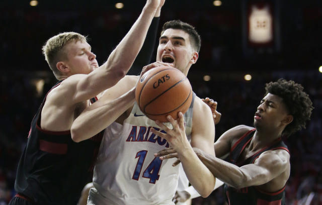 Arizona center Dusan Ristic (14) is fouled while trying to drive between Stanford's Reid Travis, left, and Daejon Davis during the second half of an NCAA college basketball game Thursday, March 1, 2018, in Tucson, Ariz. Arizona defeated Stanford 75-67. (AP Photo/Rick Scuteri)