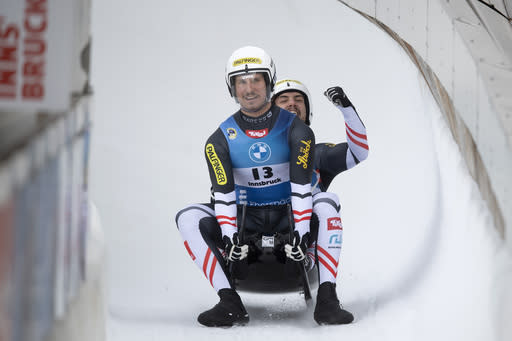 Thomas Steu and Lorenz Koller of Austria celebrate after their run in the men's doubles sprint race at the Luge World Cup event in Innsbruck, Austria, Sunday, Jan. 24, 2021. (AP Photo/Andreas Schaad)