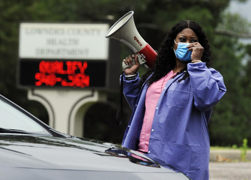 "In this May 27, 2020, photo, health care worker Tonya Wilkes adjusts her mask while working at a Lowndes County coronavirus testing site in Hayneville, Ala. Experts say Lowndes County and nearby poor, mostly black counties in rural Alabama are now facing a ""perfect storm"" as infections tick up: a lack of access to medical care combined with poverty and the attendant health problems that can worsen the outcomes for those who become sick. (AP Photo/Jay Reeves)"
