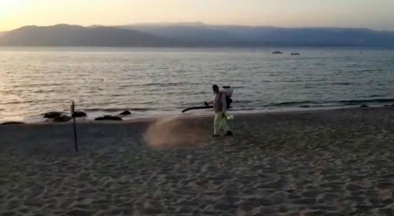 A council worker in a protective suit using a disinfectant sprayer on the beach.