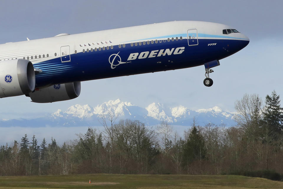 FILE - In this Jan. 25, 2020, file photo a Boeing 777X airplane takes off on its first flight with the Olympic Mountains in the background at Paine Field in Everett, Wash. Boeing will cut more jobs as it continues to lose money and revenue during a pandemic that has smothered demand for new airline planes. The company said Wednesday, Oct. 28, that it expects to cut its workforce to about 130,000 employees by the end of next year, down 30,000 from the start of this year. (AP Photo/Ted S. Warren, File)