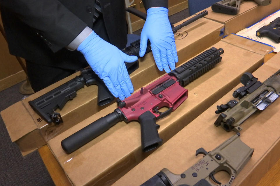 """FILE - In this file photo taken Wednesday, Nov. 27, 2019, is Sgt. Matthew Elseth with """"ghost guns"""" on display at the headquarters of the San Francisco Police Department in San Francisco. California's attorney general is suing the Trump administration in an effort to crack down on so-called """"ghost guns"""" that can be built from parts with little ability to track or regulate the owner. (AP Photo/Haven Daley,File)"""