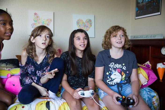 Four kids sit on a bed playing video games.