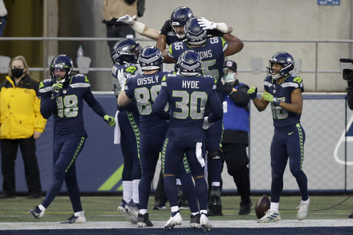 Seattle Seahawks tight end Jacob Hollister (86), top, celebrates with teammates after he caught a pass for a touchdown against the Los Angeles Rams during the second half of an NFL football game, Sunday, Dec. 27, 2020, in Seattle. (AP Photo/Scott Eklund)