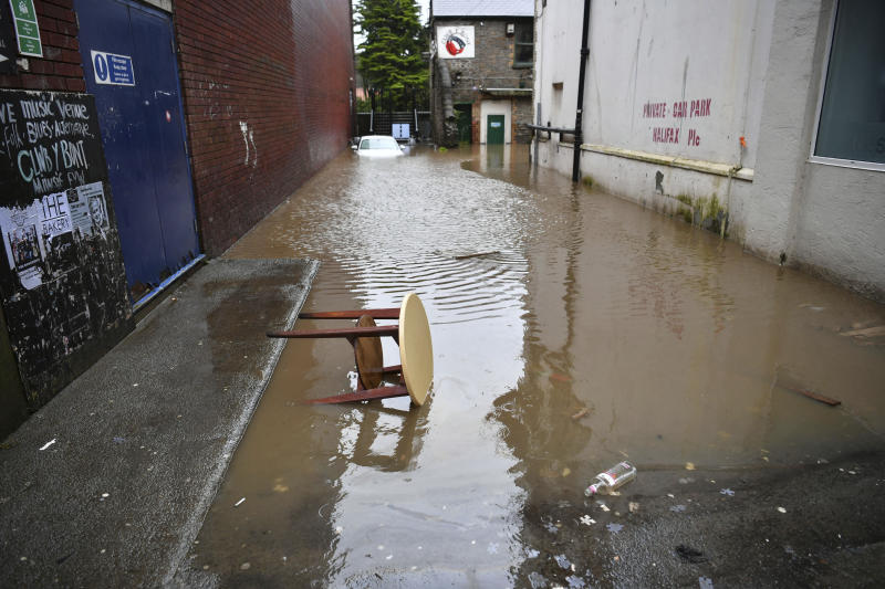 """A view of a flooded street, in Pontypridd, Wales, Sunday, Feb. 16, 2020. Storm Dennis roared across Britain with high winds and heavy rains Sunday, prompting authorities to issue some 350 flood warnings, including a """"red warning"""" alert for life-threatening flooding in south Wales. (Ben Birchall/PA via AP)"""