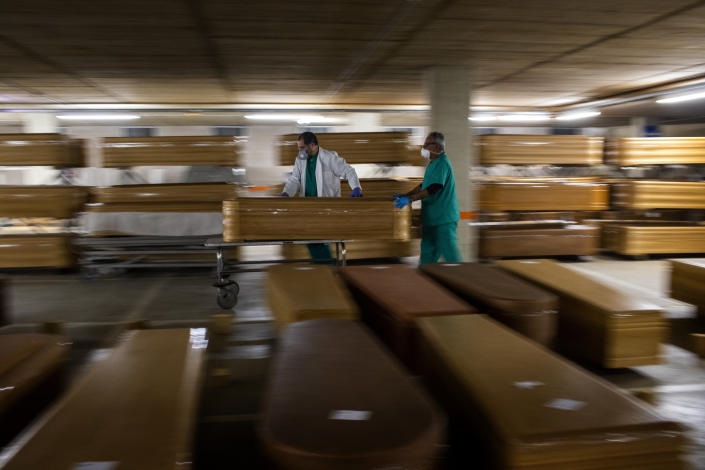Workers move a coffin with the body of a coronavirus victim at the Collserola morgue in Barcelona on April 2. (Emilio Morenatti/AP)