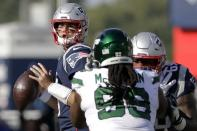 New England Patriots quarterback Jarrett Stidham, left, looks for a receiver past New York Jets defensive tackle Steve McLendon (99) in the second half of an NFL football game, Sunday, Sept. 22, 2019, in Foxborough, Mass. (AP Photo/Steven Senne)