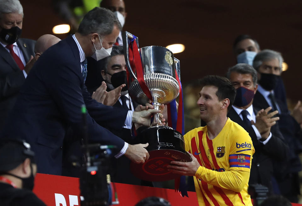 Barcelona's Lionel Messi receives the trophy by Spain's King Felipe after winning the Spanish Copa del Rey final 2021 against Athletic Bilbao at La Cartuja stadium in Seville, Spain, Saturday April 17, 2021. (AP Photo/Angel Fernandez)