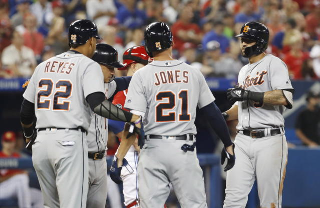 Detroit Tigers' Nicholas Castellanos, right, celebrates his grand slam with teammates JaCoby Jones, (21) Victor Reyes (22), and Jose Iglesias, against the Toronto Blue Jays during the fifth inning of a baseball action in Toronto, Sunday July 1, 2018. (Mark Blinch/The Canadian Press via AP)