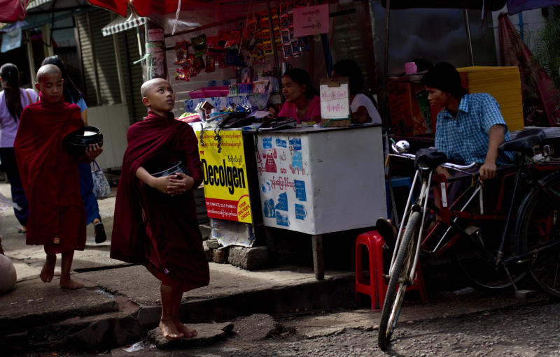 In this June 24, 2013 photo, novice Buddhist monks walk past a roadside telephone counter in Yangon, Myanmar. Foreign companies will tap into one of the world's final telecom frontiers Thursday, June 27, 2013 when Myanmar hands out licenses to operate two new mobile phone networks — part of efforts by the long-isolated nation to use technology to spur economic development. (AP Photo/Gemunu Amarasinghe)
