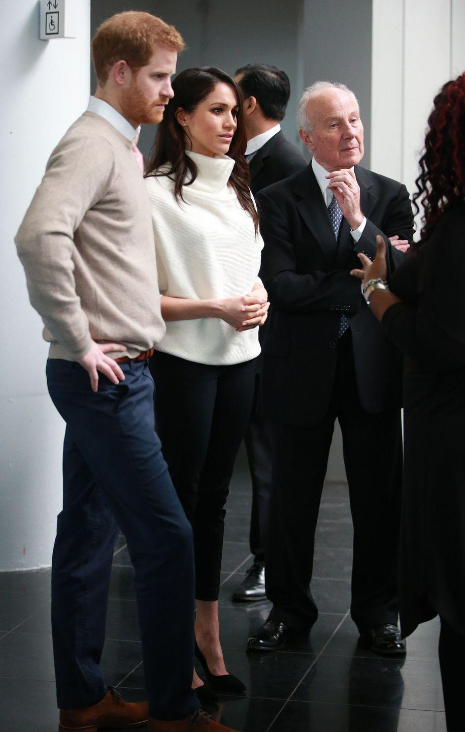 "<p>While inside Millennium Point during their royal visit to Birmingham, Markle gave us a better look at her white sweater by <a href=""https://www.allsaints.com/women/knitwear/allsaints-ridley-jumper/?colour=4068&category=26"" rel=""nofollow noopener"" target=""_blank"" data-ylk=""slk:AllSaints"" class=""link rapid-noclick-resp"">AllSaints</a> and Alexander Wang pants. </p>"