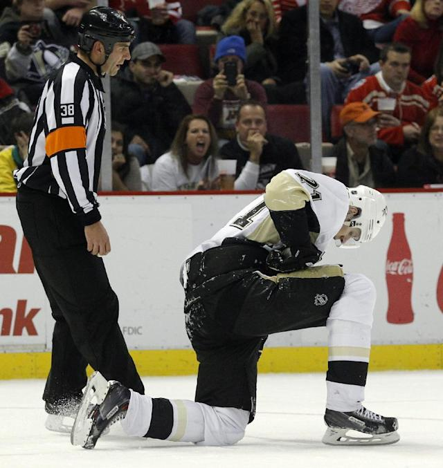 Pittsburgh Penguins' Evgeni Malkin (71) kneels on the ice after getting hit in the second period of an NHL hockey game against the Detroit Red Wings, Saturday, Dec. 14, 2013, in Detroit. (AP Photo/Duane Burleson)