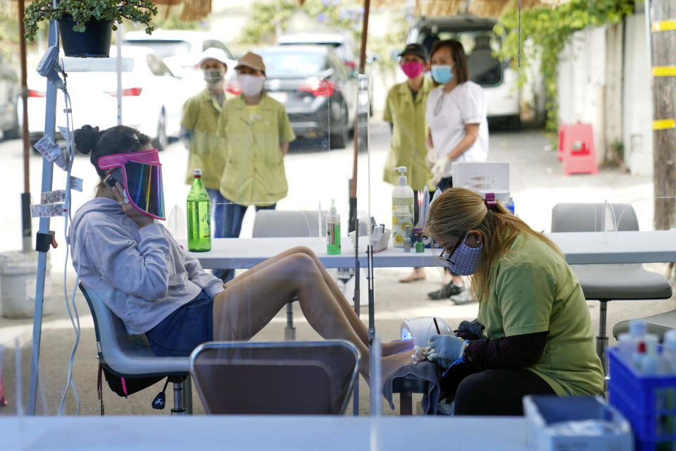 FILE - In this July 22, 2020, file photo, Tyson Salomon, left, gets a pedicure outside Pampered Hands nail salon in Los Angeles California's top health official says the state will no longer require social distancing and will allow full capacity for businesses when the state reopens on June 15, 2021. State health director Dr. Mark Ghaly said Friday, May 21, that the state envisions loosening many of its rules in mid-June as coronavirus cases continue to fall and vaccine rates continue to rise. (AP Photo/Ashley Landis, File)
