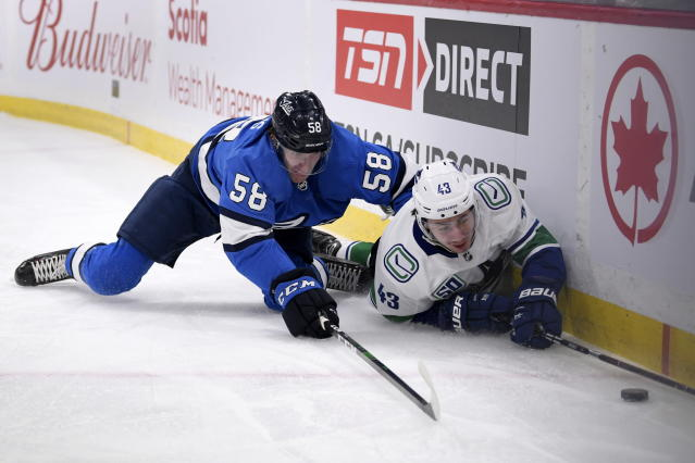 Winnipeg Jets' Jansen Harkins (58) and Vancouver Canucks' Quinn Hughes (43) battle for the puck during the second period of an NHL hockey game Tuesday, Jan. 14, 2020, in Winnipeg, Manitoba. (Fred Greenslade/The Canadian Press via AP)