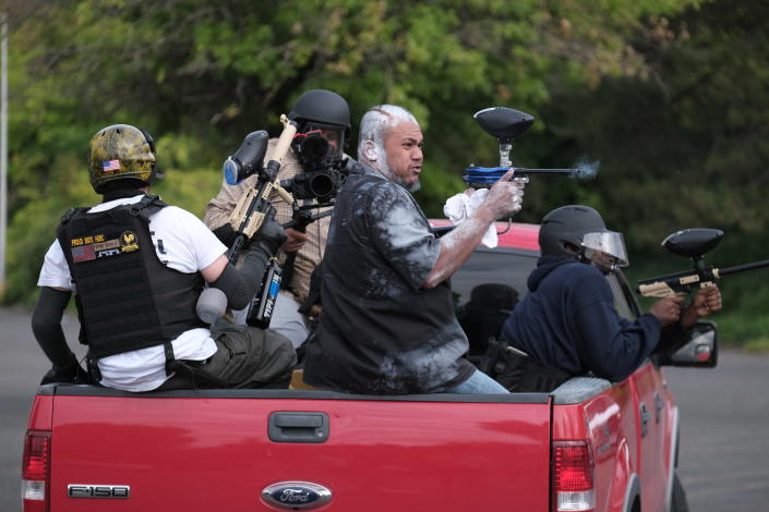 """Tusitala """"Tiny"""" Toese, a member of the far-right group Proud Boys, fires paintball rounds at anti-fascist protesters as they depart from their rally on Sunday, Aug. 22, 2021, in Portland, Ore. (AP Photo/Alex Milan Tracy)"""