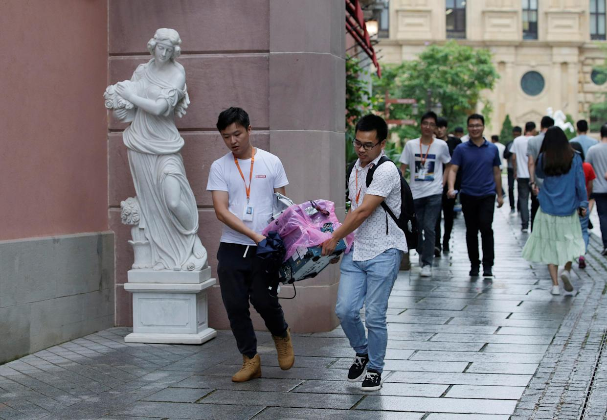 Employees carry an equipment past a sculpture at Huawei Songshan Lake New Campus in Dongguan, Guangdong province, China May 29, 2019. REUTERS/Jason Lee