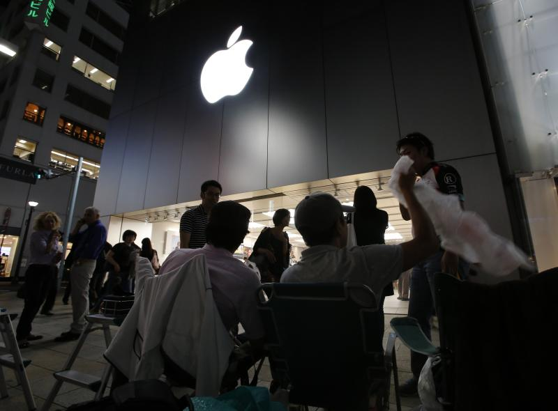 People wait for the release of Apple's new iPhone 5S and 5C in Tokyo's Ginza shopping district