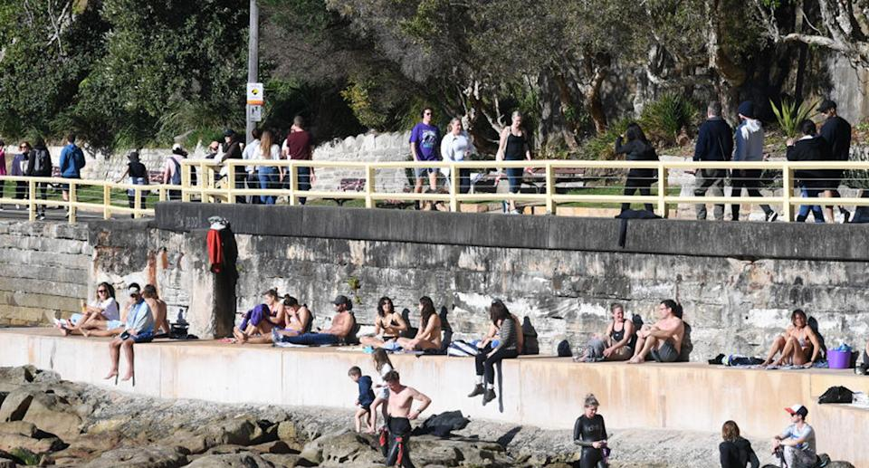 People sit on a wall at the south end of Manly beach over the weekend. Source: Getty