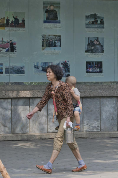 A woman carries a child past a board display with photographs of North Korea's leader Kim Jong Un outside the North Korean embassy in Beijing, China, Wednesday, May 22, 2013. North Korean leader Kim Jong Un dispatched a high-profile official and close confidant to travel to China on Wednesday as a special envoy while Beijing is under pressure to rein in its belligerent neighbor. (AP Photo/Ng Han Guan)