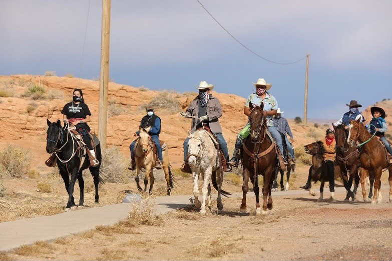 Allie Young, left, a Diné woman on the Navajo Nation in Arizona, is among a group of Native Americans as they ride on horseback to the polls on Election Day in Kayenta, Ariz., Tuesday, Nov. 3, 2020. (Larry Price via AP)