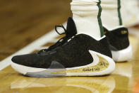 The shoes of Milwaukee Bucks' Giannis Antetokounmpo are seen with a message honoring Kobe Bryant, during the first half of the Bucks' NBA basketball game against the Denver Nuggets on Friday, Jan. 31, 2020, in Milwaukee. (AP Photo/Aaron Gash)