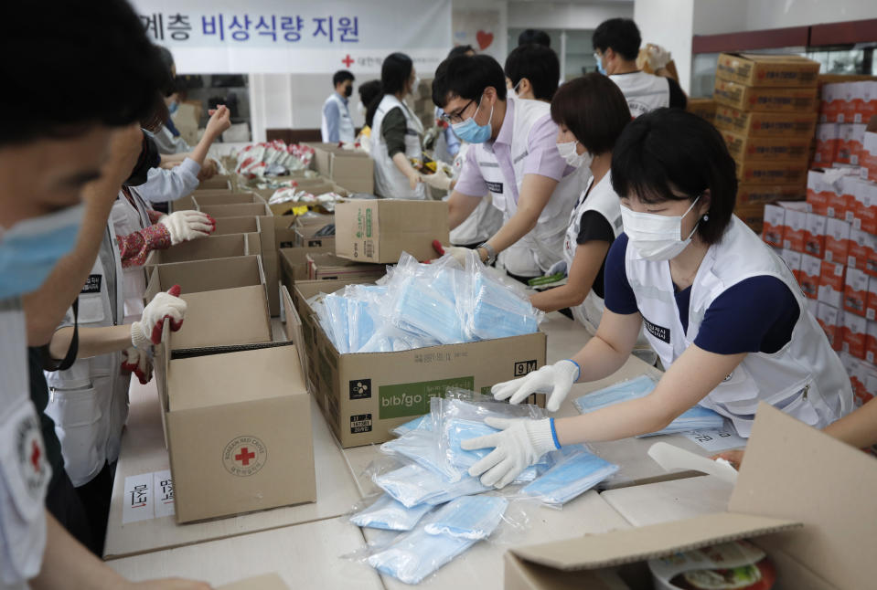 Red Cross workers prepare emergency relief kits packed with instant foods and masks for delivery to impoverished people at a facility of the Korean National Red Cross in Seoul, South Korea, Wednesday, June 3, 2020. (AP Photo/Lee Jin-man)