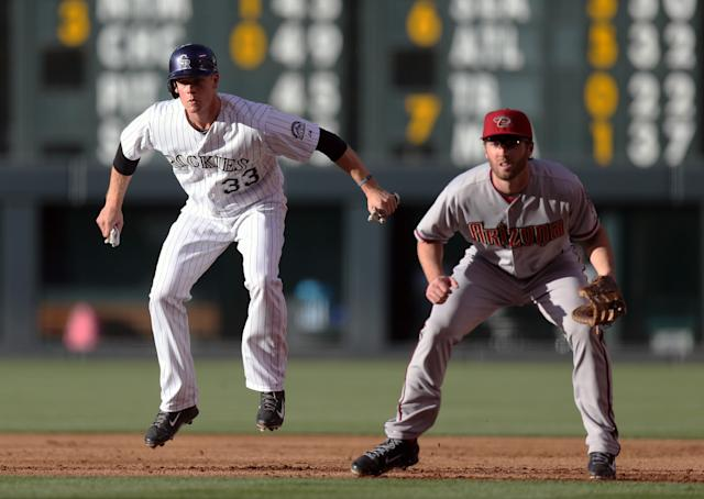 Colorado Rockies base runner Justin Morneau, left, jumps in the air as he takes a lead off first base as Arizona Diamondbacks first baseman Nick Evans covers in the first inning of a baseball game in Denver on Tuesday, June 3, 2014. (AP Photo/David Zalubowski)